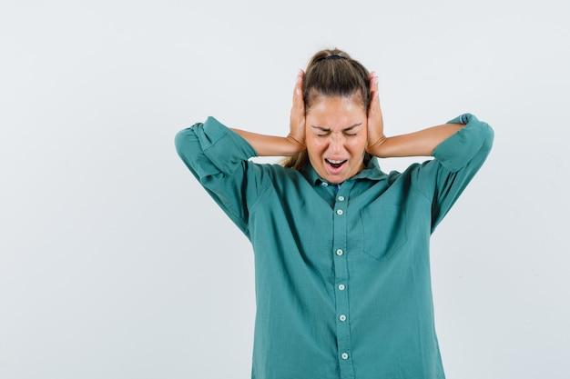 Молодая женщина в зеленой блузке сжимает руки уши и выглядит взволнованной