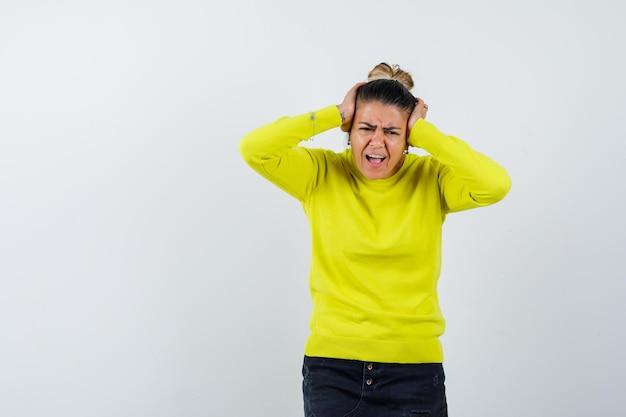 若い女性は耳に手を押して、黄色いセーターと黒いズボンで口を大きく開いたままにして、急いでいるように見えます