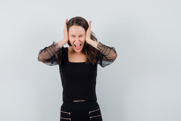Молодая женщина зажимает уши руками и кричит в черной блузке и черных штанах и выглядит разъяренной, вид спереди.