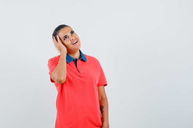 Young woman pressing palm on ear in red shirt and looking excited , front view.