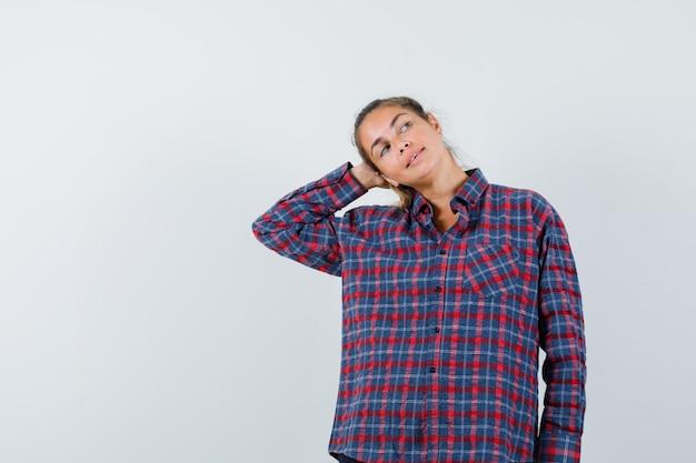 Молодая женщина прижимает ладонь к уху, думает о чем-то в клетчатой рубашке и выглядит задумчиво