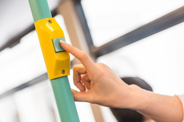 Young woman pressing stop request button on the bus