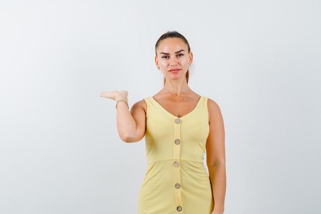 Молодая женщина делает вид, что держит что-то в желтом платье и выглядит уверенно