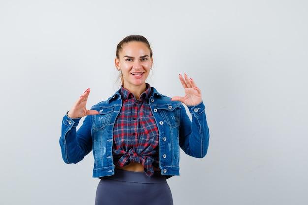Молодая женщина делает вид, что держит что-то в клетчатой рубашке, джинсовой куртке и выглядит привлекательно, вид спереди.