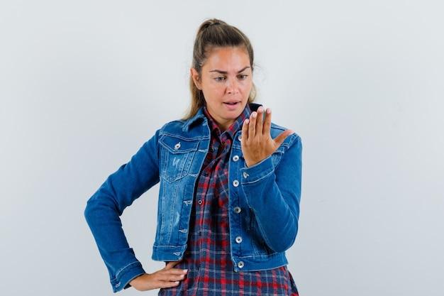 Молодая женщина делает вид, что смотрит на мобильный телефон в рубашке, куртке и выглядит смущенным. передний план.