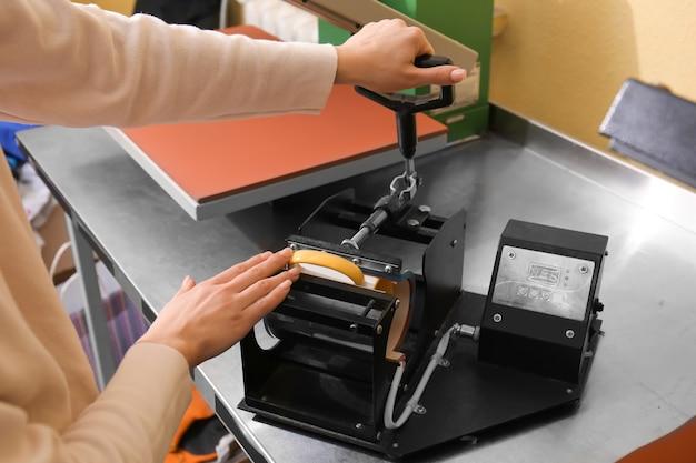 ワークショップでカップに印刷する若い女性