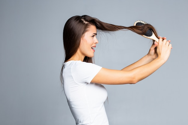 Young woman problems with hair, split weak hair, tangled hair isolated on gray