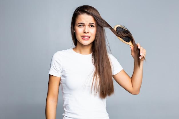 Problemi di giovane donna con i capelli, capelli spaccati, capelli arruffati isolati su grigio