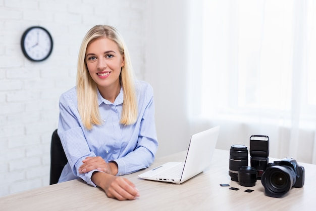 Young woman professional photographer with camera computer and photography equipment