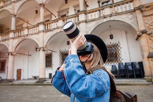 Young woman, professional photographer with camera in old castle.