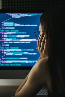 Молодая женщина-программист пишет программный код на компьютере