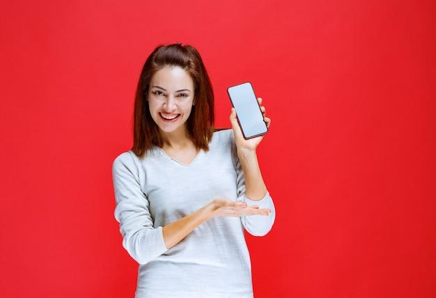Giovane donna che promuove il nuovo modello di un marchio di smartphone
