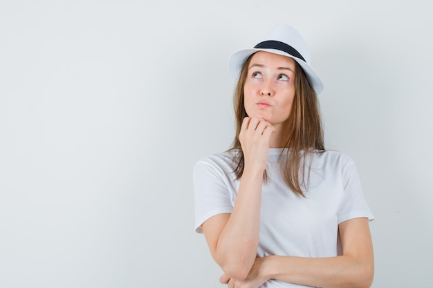 Giovane donna appoggiando il mento a portata di mano in maglietta bianca, cappello e guardando indeciso.