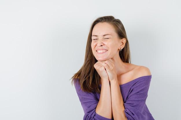 Молодая женщина подпирает подбородок сложенными руками в фиолетовой рубашке и выглядит счастливой. передний план.