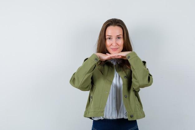 シャツ、ジャケットのくいしばった指であごを支え、かわいく見える若い女性。正面図。