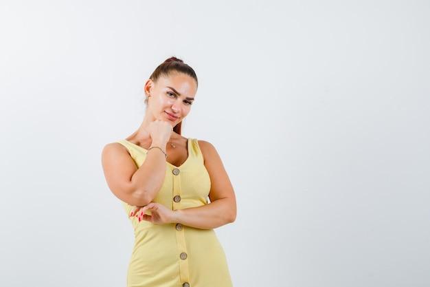 黄色いドレスを着て拳で顎を支え、賢明に見える若い女性。正面図。