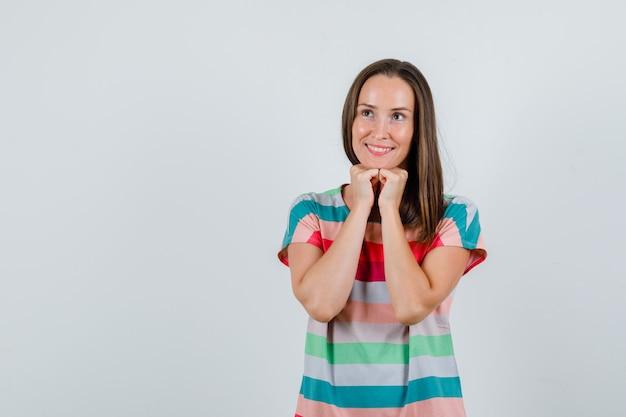 Tシャツの拳で顎を支え、希望に満ちた正面図を探している若い女性。
