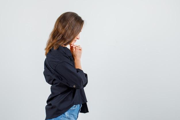 シャツ、ショートパンツで見下ろし、平和に見えながら、拳で顎を支えている若い女性。