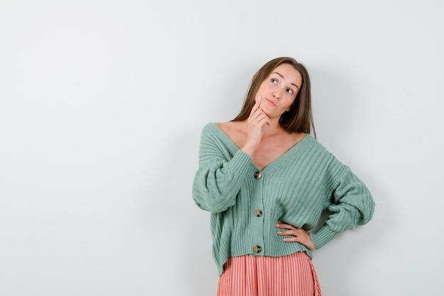 カーディガン、スカート、夢のような、正面図で手に顎を支えている若い女性。 無料写真