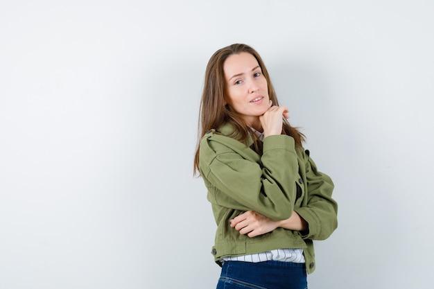 シャツ、ジャケット、そして賢明な正面図で手に顎を支えている若い女性。
