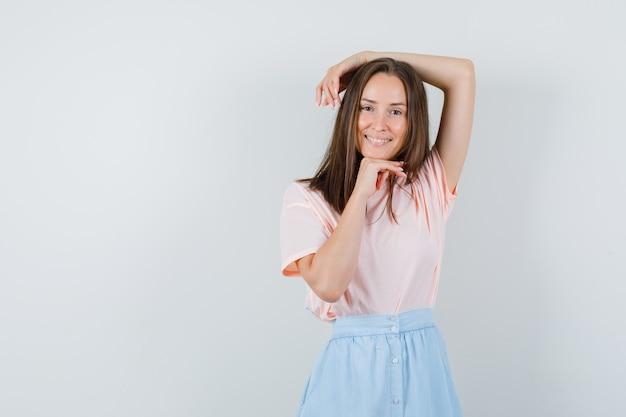 Молодая женщина подпирает подбородок рукой с протянутой рукой в футболке, юбке и выглядит веселой. передний план.