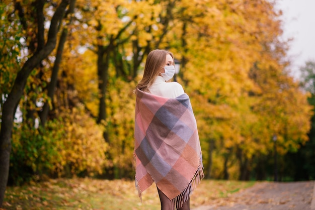 A young woman protecting from corona virus when walking in park. autumn background.