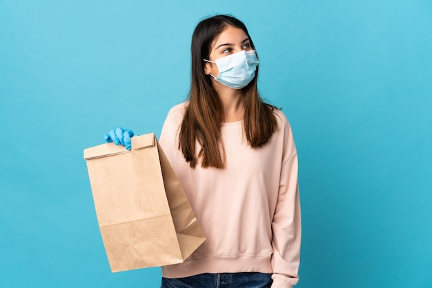 Young woman protecting from the coronavirus with a mask and holding a grocery shopping bag isolated on blue looking up while smiling