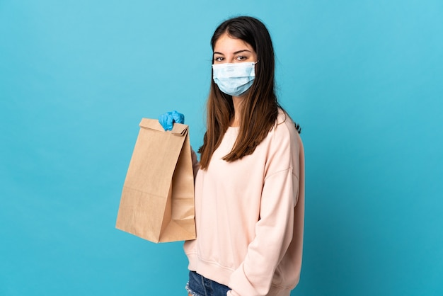 Young woman protecting from the coronavirus with a mask and holding a grocery shopping bag isolated on blue smiling a lot