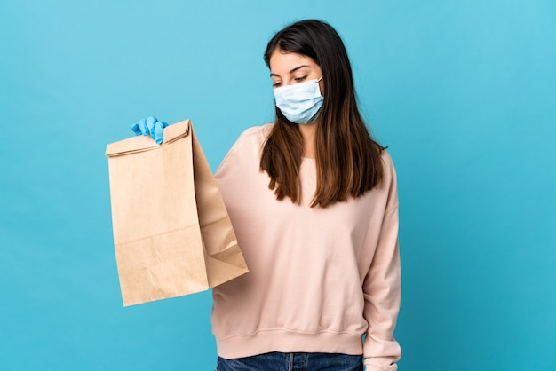 Young woman protecting from the coronavirus with a mask and holding a grocery shopping bag isolated on blue with happy expression