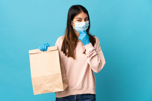 マスクでコロナウイルスから保護し、アイデアを考えて側面を見て青い壁に隔離された食料品の買い物袋を保持している若い女性