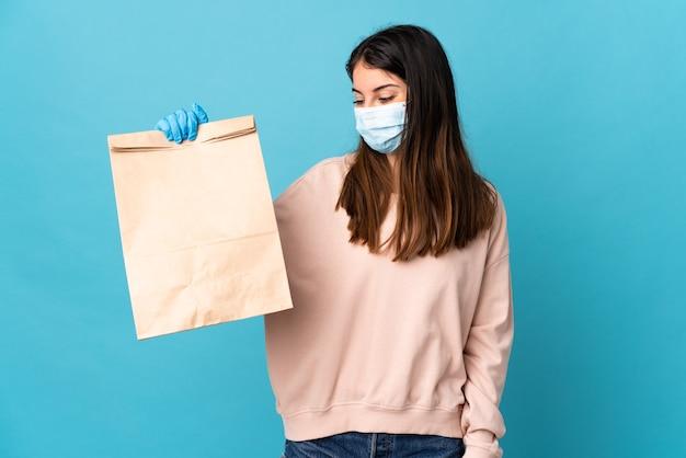 마스크로 코로나 바이러스로부터 보호하고 행복한 표정으로 파란색 벽에 고립 된 식료품 쇼핑 가방을 들고 젊은 여자