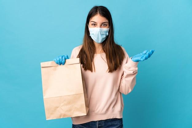Молодая женщина, защищающаяся от коронавируса с помощью маски и держащая сумку для покупок, изолирована на синей стене с шокированным выражением лица
