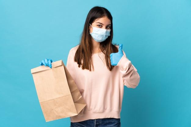 何か良いことが起こったので、マスクでコロナウイルスから保護し、親指を立てて青い壁に隔離された食料品の買い物袋を保持している若い女性