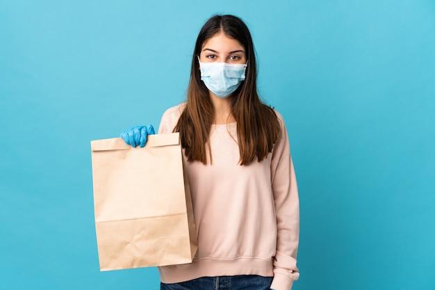Молодая женщина, защищая от коронавируса с маской и проведение продуктовых корзина, изолированных на синем с удивлением и шокирован выражением лица