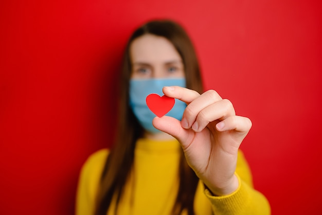 Young woman in protective blue medical mask, isolated on red background, holding red heart a way to show appreciation and to thank all essential employees during covid-19 pandemics. selective focus