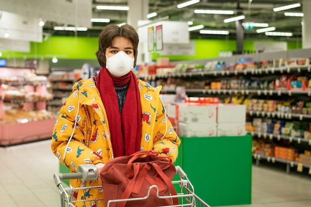 Young woman in a protective mask chooses alcohol in a supermarket, stocks are quarantined