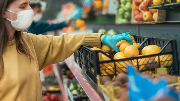 Young woman in a protective mask choosing lemons in a store. coronavirus in the city