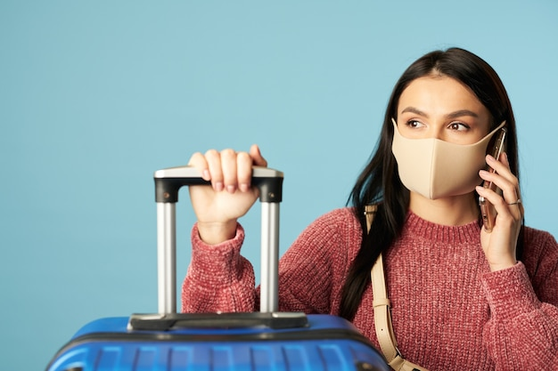 Young woman in protective mask from virus and speaking on the mobile phone while expecting flight on blue background. copy space. concept of travel, coronavirus