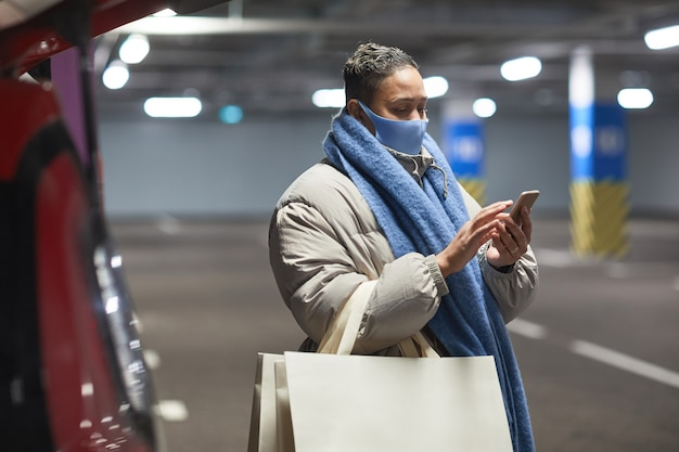 Young woman in protective mask with shopping bags using mobile phone while standing in an underground parking