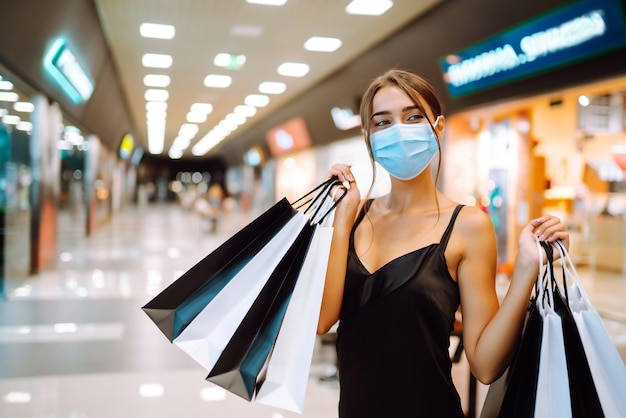 Young woman in protective sterile medical mask on her face with shopping bags in the mall.