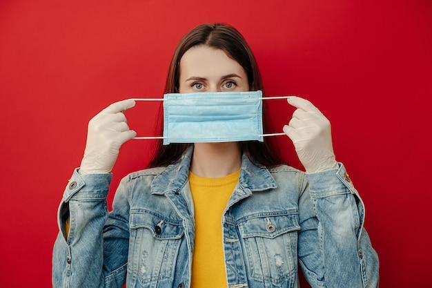 若い女性はマスクで顔を保護し、流行病の危険を冒していると考え、ウイルスに感染しており、赤い壁に隔離されたカメラを見ています。コンセプトの安全性、流行、コロナウイルス、ウイルス保護