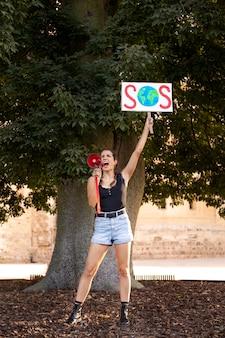 気候変動に反対するsosサインで抗議する若い女性