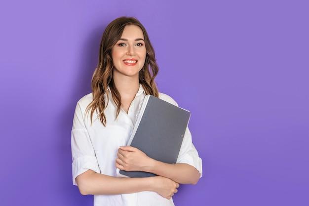 Улыбка психолога молодой женщины смотрит на камеру изолированную на предпосылке студии сирени. копировать пространство