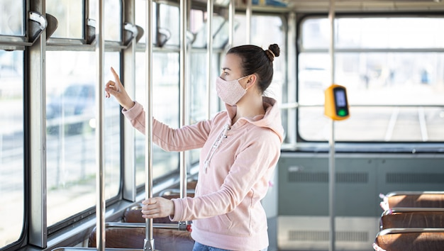 Young woman on public transport during the pandemic.