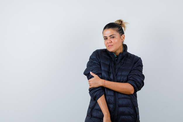 Giovane donna in piumino con la mano sul braccio e guardando fiducioso, vista frontale.