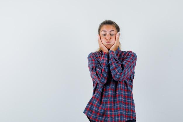 Giovane donna sbuffando guance e tenendo le mani sulla guancia in camicia a quadri e guardando divertito