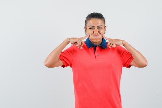 Giovane donna sbuffando le guance, tenendo il dito indice vicino alla bocca in maglietta rossa e guardando piuttosto. vista frontale.
