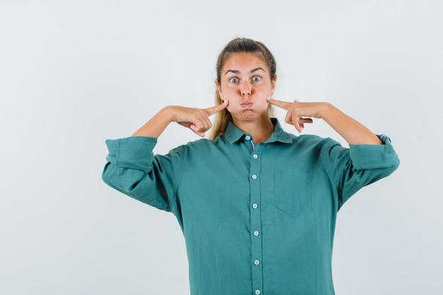 Giovane donna sbuffando guance e indicando le guance con il dito indice in camicetta verde e guardando carino