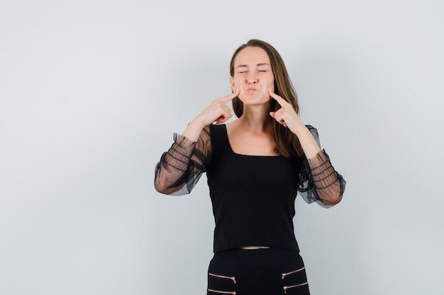 Giovane donna sbuffando guance e mettendo le dita indice sulle guance in camicetta nera e pantaloni neri e guardando divertito, vista frontale.