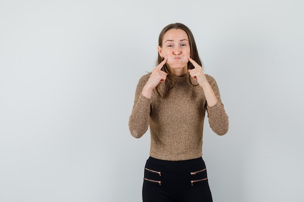 Giovane donna sbuffando le guance e mettendo le dita indice sulle guance in maglione dorato e pantaloni neri e guardando divertita. vista frontale.